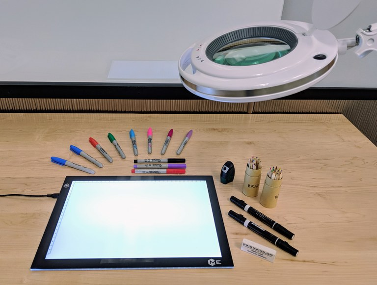 photo of drawing tools, including lighted tracing board, colored pencils, and markers