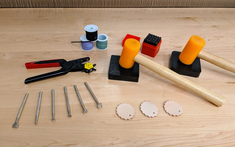 photo of tools used to work with leather projects, including mallets, leather stamps, and stamping pads.