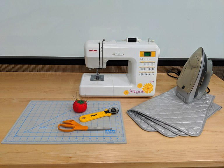 photo of sewing tools, including a sewing machine, scissors, roller cutter, cutting mat, and iron