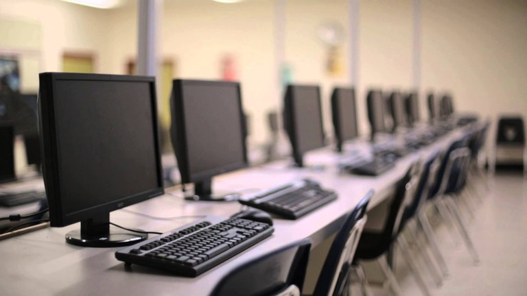A row of desktop computers in a  classroom..