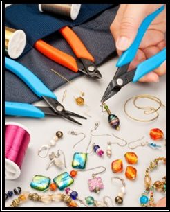 Various pliers, beads, and wires used for making jewelry.