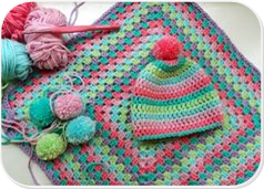 Multicolored knitted hat and blanket with yarn and knitting needles