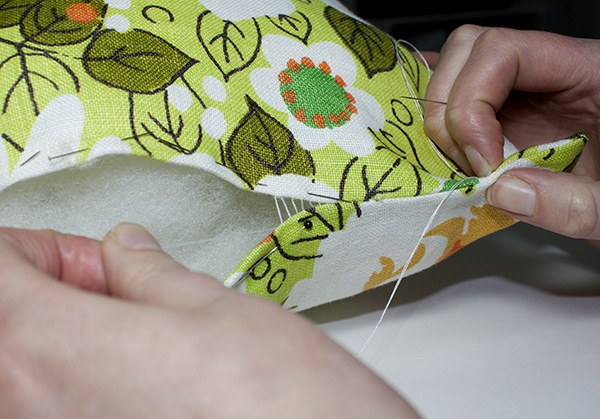 Hands sewing a pillow closed.