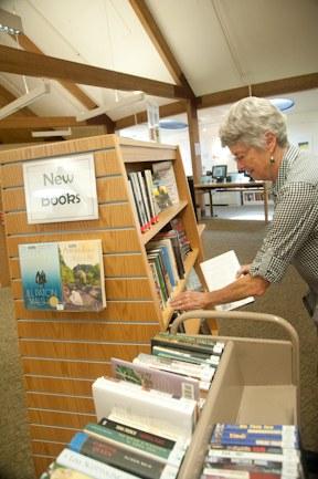 Library volunteer putting books onto shelves.